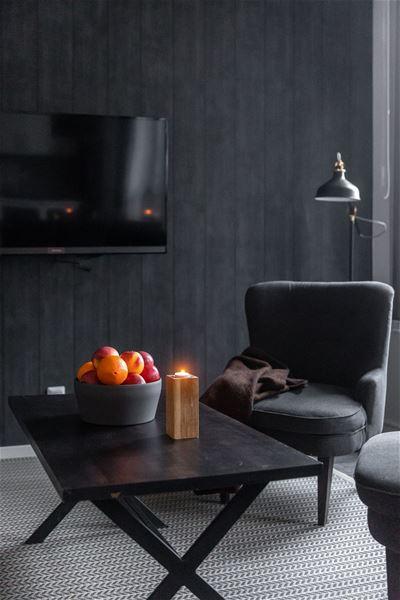 Fåtöljer och ett soffbord, tv på väggen.