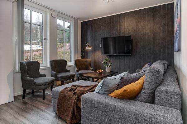 Vardagsrum med soffa, fåtöljer och en tv.