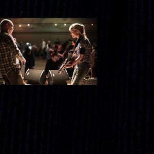 Två personer som tittar på varandra och spelar instrument.