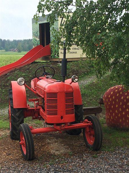Röd traktor, i bakgrunden en orange rutschkna.