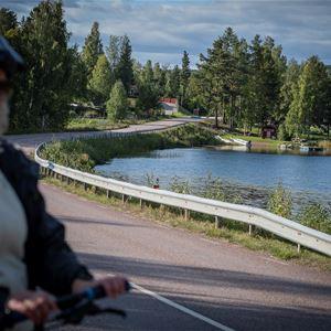 Kvinna med cykel står på en väg, sjö och träd.