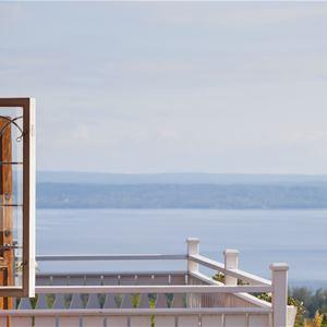 Utsikt över Siljan från en balkong med öppen dörr.