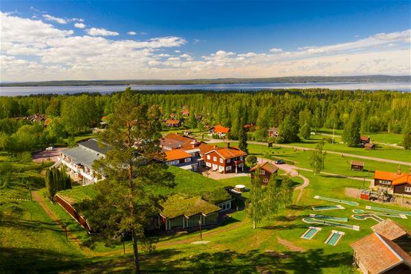 Flygfoto över röda byggnader, träd och sjön Siljan i horisonten.