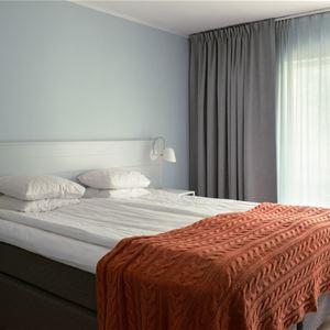 Dubbelsäng med ett orangefärgat överkast och ett fönster med gråa gardiner.