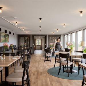 Restaurang med en hel fönstervägg och stolar och bord i trä och svart.