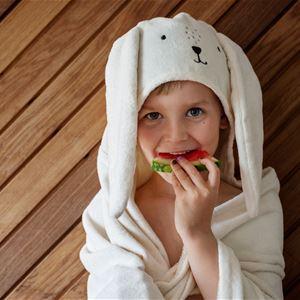 Ett barn i badrock som äter melon.