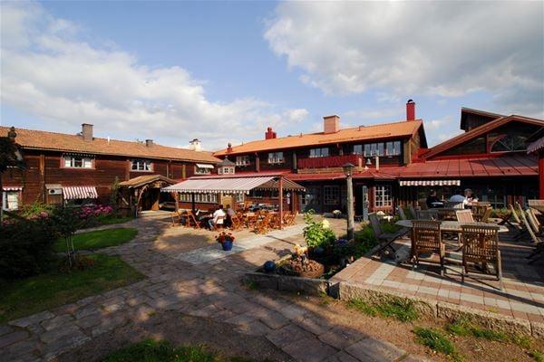 Bruna timmerhus med rött tegeltak och terrasser.