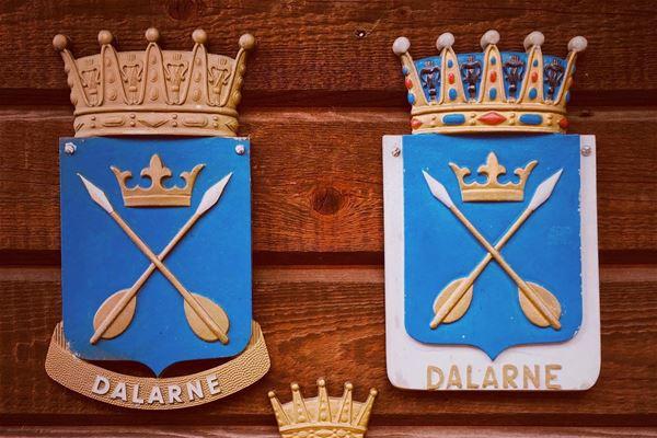 Dalarnas landskapsvapen med två korslagda pilar i guld mot en blå bakgrund.