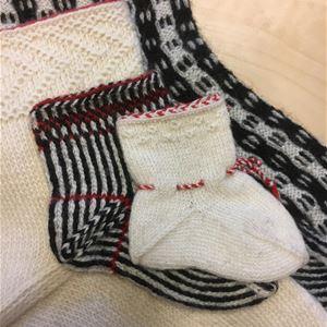 Två bebissockor en vit och en svart vit randig, två större sockor en vit och en svart vit, alla fyra stickade i tekniken tåändsstickning.
