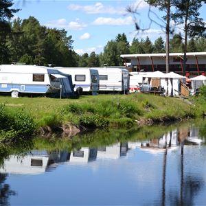 Husvagnar uppställda på camping längs en å.