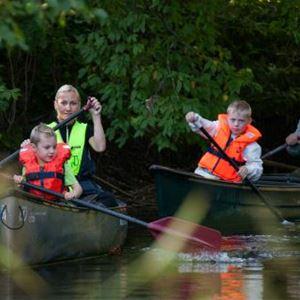 Familj som paddlar kanot i å.