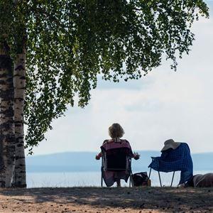 Par som sitter vid solstolar vid Siljandbadets strand.
