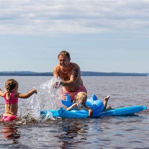 Familj som leker i sjön Siljan vid Siljanbadets Camping.