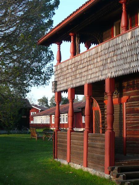 Detalj på takad uteplats och balkong med röda pelare.